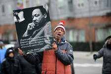 "Cornell Davis sings ""We Shall Not Be Moved"" while holding up a quote from Dr. Martin Luther King Jr. while participating in the annual Martin Luther King Jr. Day march in Stamford, Conn. on Monday, Jan. 15, 2018."