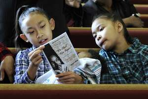 Leilany Miller, 9, left, holding seven-month-old brother Jaqeem, and sister Camille, 11, look over the program before the start of Monday's tribute to the Rev. Dr. Martin Luther King, Jr. at New Hope Baptist Church, in Danbury, Monday, January 15, 2018.
