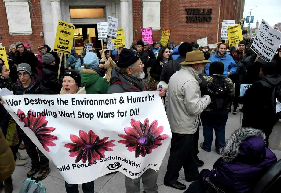 Dakota Access Pipeline protesters demonstrate in front of a Wells Fargo bank branch on the corner of College and Elm Streets in Jan. 2017, in New Haven. Local residents are seeking a public hearing urging the city to move its public funds from the bank. Photo: Peter Hvizdak / Hearst Connecticut Media / ©2017 Peter Hvizdak
