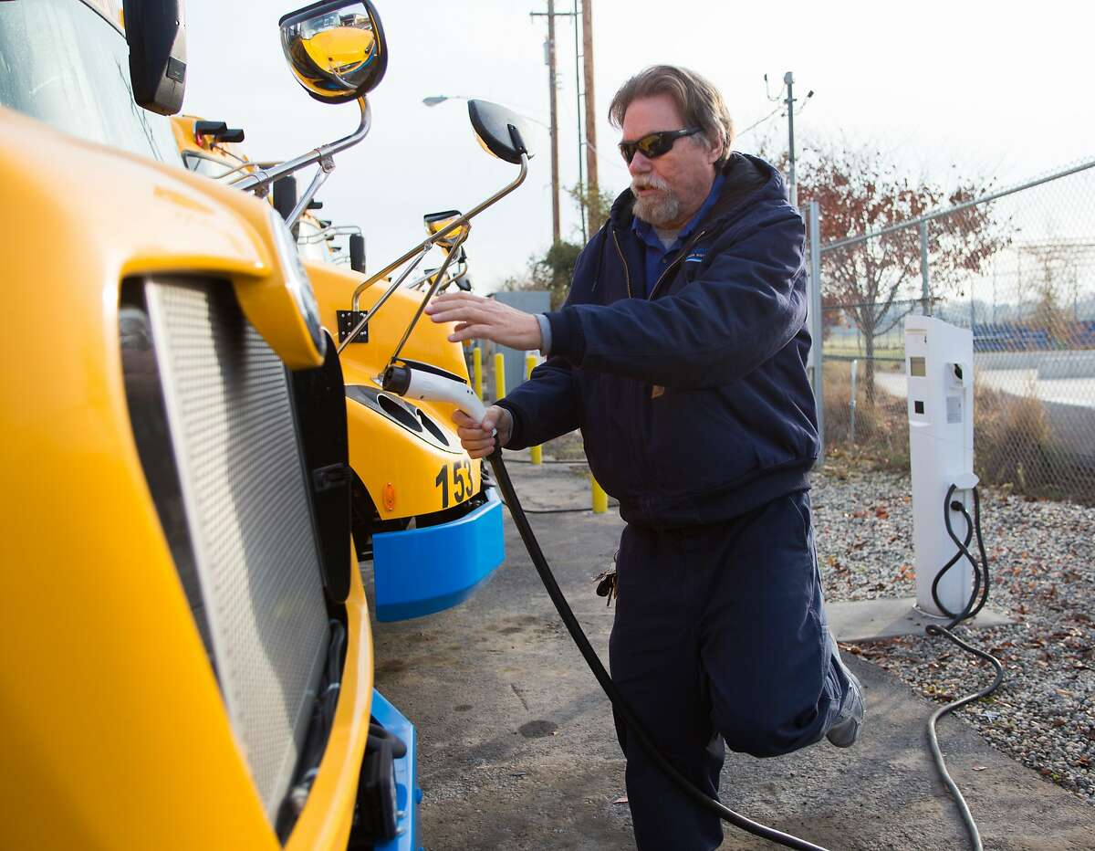Richard Thomas, a bus driver in Sacramento for the past 12 years, plugs in an electric bus after finishing his route in Sacramento, California, Friday, December 15, 2017.