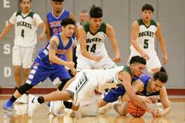 Memorial's Brandon Rodriguez (lower right) and Kennedy's Michael Puente fight for a loose ball during the first half of their District 28-5A boys basketball game at the Edgewood Gym  Jan. 12. Kennedy beat Memorial 64-62.