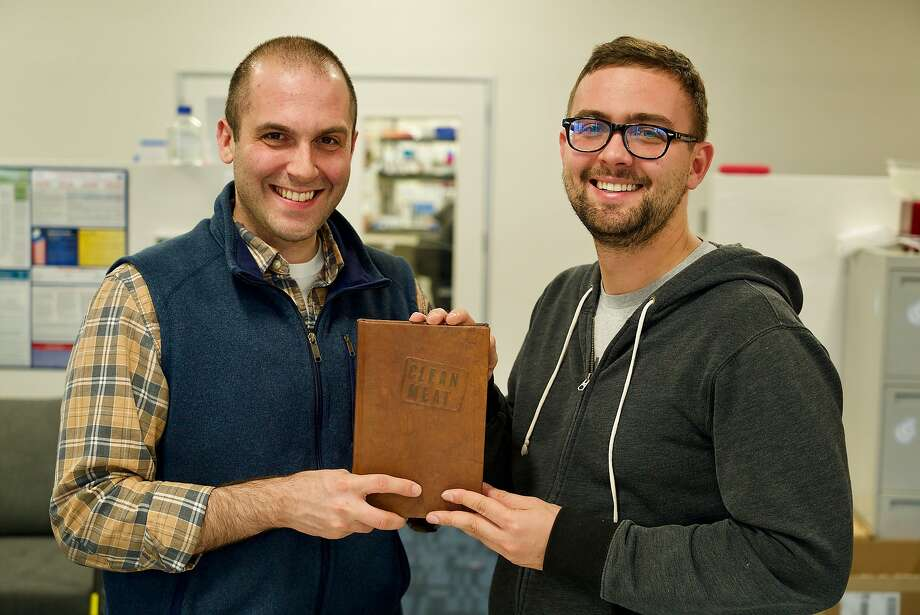 """Geltor co-founders Alexander Lorestani (left) and Nick Ouzounov hold a copy of Paul Shapiro's book """"Clean Meat,"""" about cultured meat. Geltor, which manufactures collagen for cosmetics from yeast cells, produced one leather-bound copy of the book using cultured leather. Photo: Eric Day"""