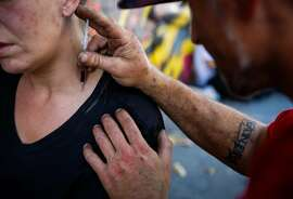 Shawn attempts to inject Molly with heroin in her neck on Larkin Street in San Francisco, Calif., on Thursday, Oct. 26, 2017.
