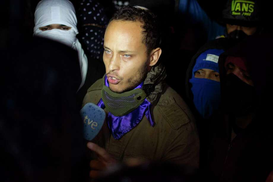 FILE - In this July 13, 2017 file photo, Oscar Perez speaks to the press at a night vigil to honor the more than 90 people killed during three months of anti-government protests, in Caracas, Venezuela. Venezuelan officials say on Monday, Jan. 15, 2018 they've exchanged fire during an attempt to capture the fugitive police officer who led a high-profile attack in Caracas last year from a stolen helicopter. (AP Photo/Miguel Rodriguez, File) Photo: Miguel Rodriguez, STR / Copyright 2017 The Associated Press. All rights reserved.