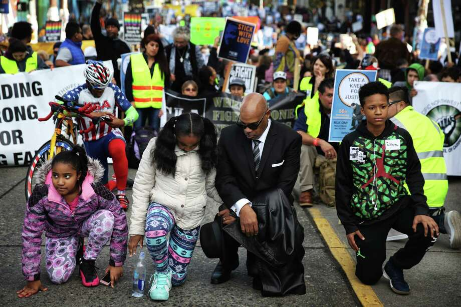 Rev. Dr. George E. Noble kneels with his granddaughters, Alana Edwards, 11, and Aleena Edwards, 9, during the annual Martin Luther King Day march from Garfield High School to Westlake Park, Monday, Jan. 15, 2018. Photo: GENNA MARTIN, SEATTLEPI.COM / Seattlepi.com