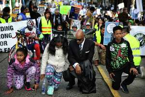 Rev. Dr. George E. Noble kneels with his granddaughters, Alana Edwards, 11, and Aleena Edwards, 9, during the annual Martin Luther King Day march from Garfield High School to Westlake Park, Monday, Jan. 15, 2018.