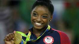 FILE - In this Aug. 16, 2016 file photo, United States gymnast Simone Biles displays her gold medal for floor during the artistic gymnastics women's apparatus final at the 2016 Summer Olympics in Rio de Janeiro, Brazil. In a statement via Twitter on Monday, Jan. 15, 2017, Biles says she is among the athletes sexually abused by a now-imprisoned former USA Gymnastics team doctor.. (AP Photo/Rebecca Blackwell, File)