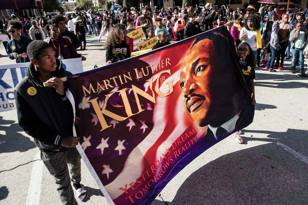 Students from KIPP Houston carry a banner featuring Dr. Martin Luther King, Jr., during The
