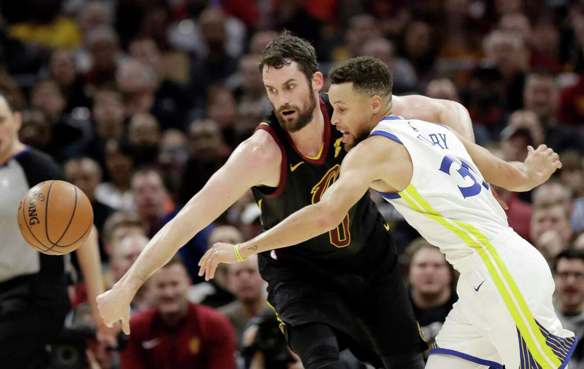 Cleveland Cavaliers' Kevin Love, left, and Golden State Warriors' Stephen Curry battle for the ball in the first half of an NBA basketball game, Monday, Jan. 15, 2018, in Cleveland.
