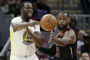 Golden State Warriors' Draymond Green, left, passes against Cleveland Cavaliers' LeBron James in the first half of an NBA basketball game, Monday, Jan. 15, 2018, in Cleveland. (AP Photo/Tony Dejak)
