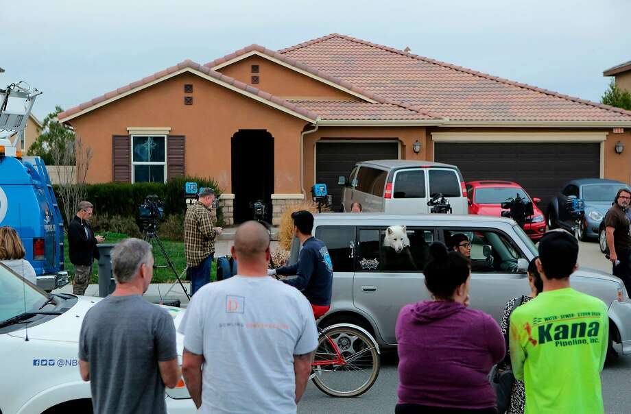 Residents of Perris (Riverside County) watch as media gather in front of the home where 13 children and young adults were suspected of being held captive. Photo: BILL WECHTER, AFP/Getty Images