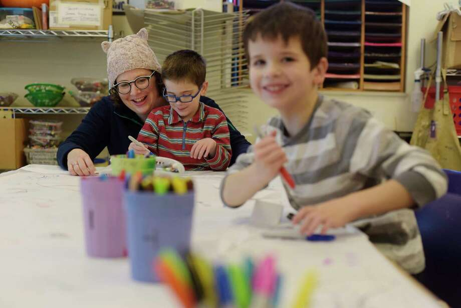 Beth MacCallum of Albany and her sons, George, 4, and Henry, 6, work on making suffrage sashes during a free admission day at the Albany Institute of History and Art on Monday, Jan. 15, 2018, in Albany, N.Y.  Guests could make their own suffrage sashes and art event connected to the institute's exhibit entitled, Albany and Anti-Suffrage.  (Paul Buckowski/Times Union) Photo: PAUL BUCKOWSKI / (Paul Buckowski/Times Union)