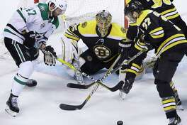 Dallas Stars right wing Alexander Radulov, of Russia, left, vies for control of the puck with Boston Bruins center Patrice Bergeron, right, as Bruins goaltender Anton Khudobin, center, guards the net in the third period of an NHL hockey game, Monday, Jan. 15, 2018, in Boston. The Stars won 3-2 in overtime. (AP Photo/Steven Senne)