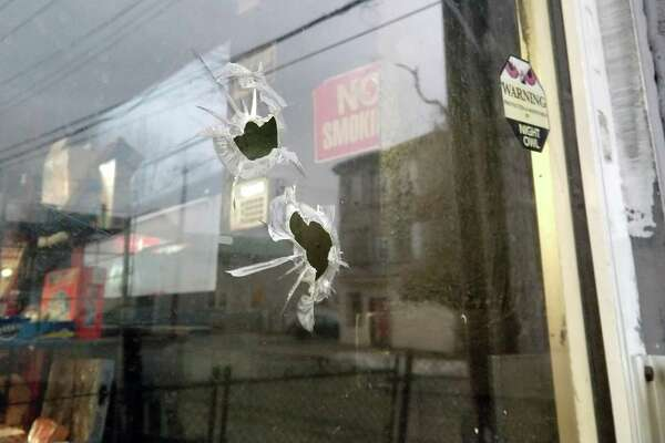 Bullet holes identified by a worker at the Snack Shop, where a customer was shot and killed Tuesday, Jan.16, 2018 in Bridgeport, Conn. It was the city's first homicide of the year.