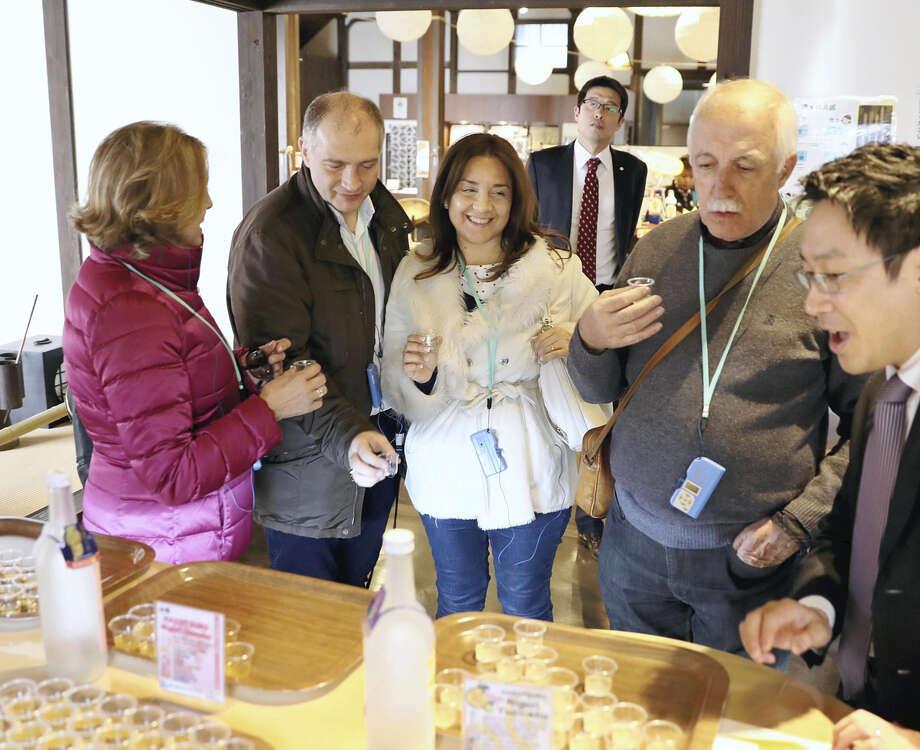 Foreign visitors try sake at the Hakutsuru Sake Brewery Museum in Higashinada Ward, Kobe, Japan. Photo: Japan News-Yomiuri / Japan News-Yomiuri