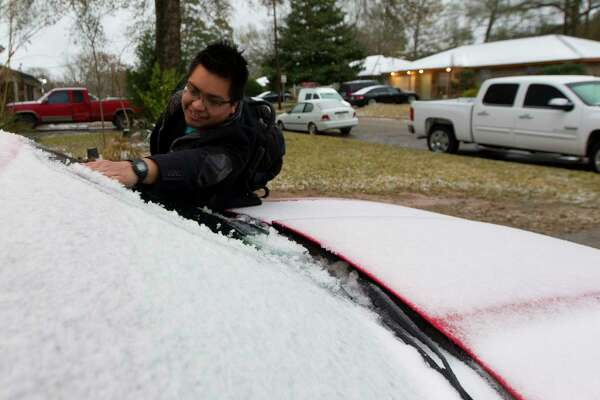 Luis Benitez removes ice from his car as heads to his job at Conroe Regional Medical Center while he and other residents wake up to the effects of a winter storm that brought freezing rain and ice through Montgomery County, Tuesday, Jan. 16, 2018. The National Weather Service issued a Winter Storm Warning for southeast Texas until midnight Wednesday.