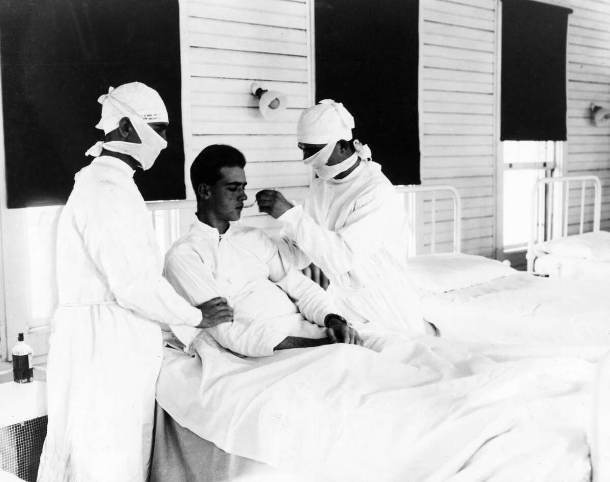 circa 1918: Doctors giving treatment to an influenza patient at the US Naval Hospital in New Orleans.