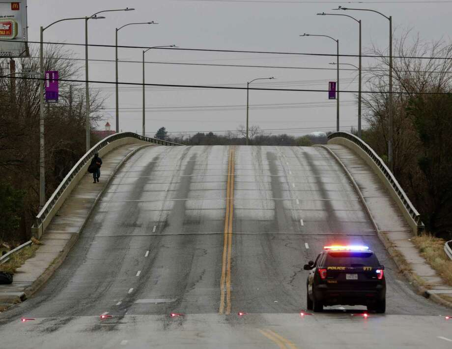 A man walks across the N. Walters Street overpass near Interstate 35 where a police car blocks the road due to icy conditions. Photo: Bob Owen /San Antonio Express-News / San Antonio Express-News