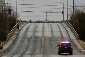 A man walks across the N. Walters Street overpass near Interstate 35 where a police car blocks the road due to icy conditions.