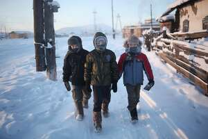A trio of young boys walk through Oymyakon. They are wearing warm clothing.