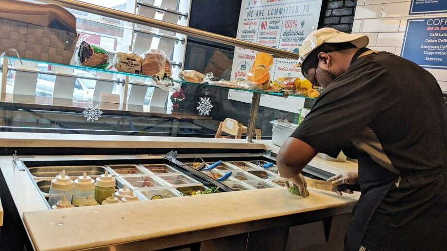 Dwayne Frankin, a culinary trained line cook, chops fresh avocado for a chicken quesadilla on the grill at Grown in the Wesleyan RJ Julia Bookstore in Middletown. Photo: Sloan Brewster Photo