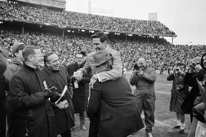 """Alabama coach Paul """"Bear"""" Bryant, hat, rushes over to the Texas A&M bench and picks up coach Gene Stallings and carries him off the field as a gesture of congratulations after the Aggies defeated the Crimson Tide, 20-16, in the Cotton Bowl Classic in Dallas, Texas, Jan. 1, 1968. Stallings played under Bryant as a collegian and served under him as an assistant coach. Reporters enjoy the activity. (AP Photo)"""
