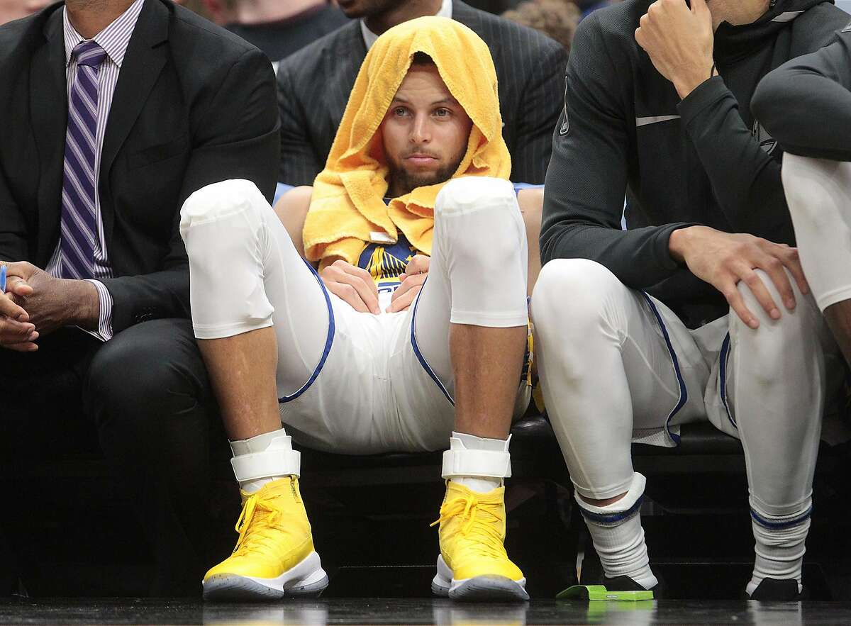 Golden State Warriors guard Stephen Curry sits on the bench in the fourth quarter in Cleveland.