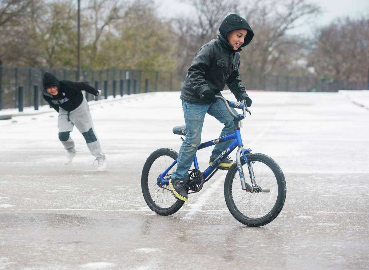 Brothers Benny Rodriguez, 12, and David Rodriguez, 9, play in the ice covered parking lot of their school, Bonner Elementary, in Tyler, Texas on Tuesday Jan. 16, 2018. An overnight winter storm brought unusually cold temperatures, ice and snow to the East Texas region. Tyler Independent School District was closed for the inclement weather. (Sarah A. Miller/Tyler Morning Telegraph)