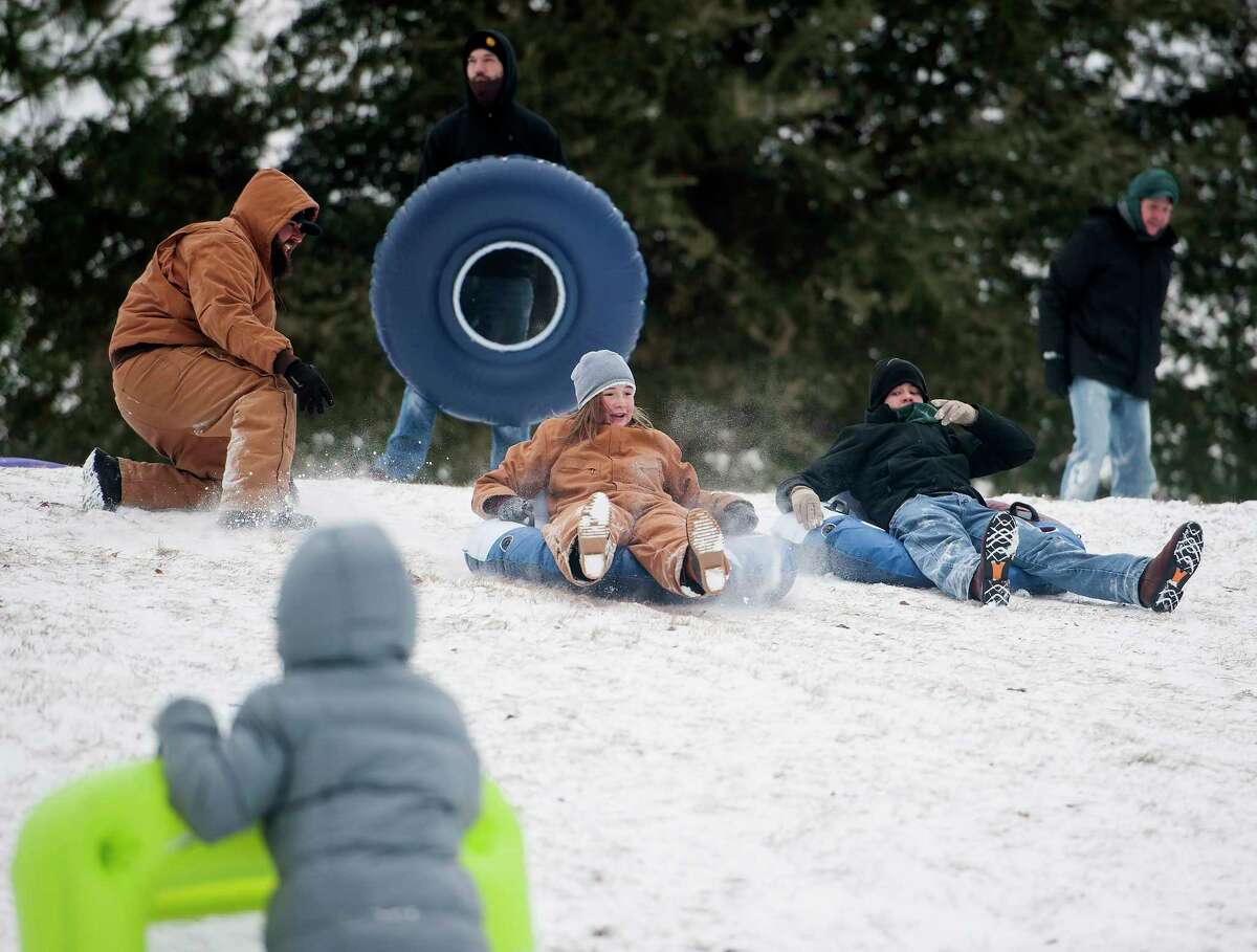 Emma Carver, 12, center, sleds down a snowy hill on the campus of the University of Texas at Tyler in Tyler, Texas on Tuesday Jan. 16, 2018. An overnight winter storm brought unusually cold temperatures, ice and snow to the East Texas region. (Sarah A. Miller/Tyler Morning Telegraph via AP)