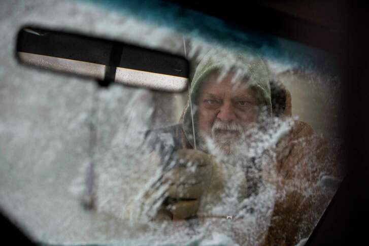 CORRECTS SPELLING TO FALSETTI NOT FALSETTO - Mike Falsetto cleans the ice from his windshield Friday, Jan. 12, 2018, in South Bend, Ind. Friday's return of cold temperatures, ice and snow was a contrast with Thursday's record breaking high temperatures in South Bend. (Santiago Flores/South Bend Tribune via AP)