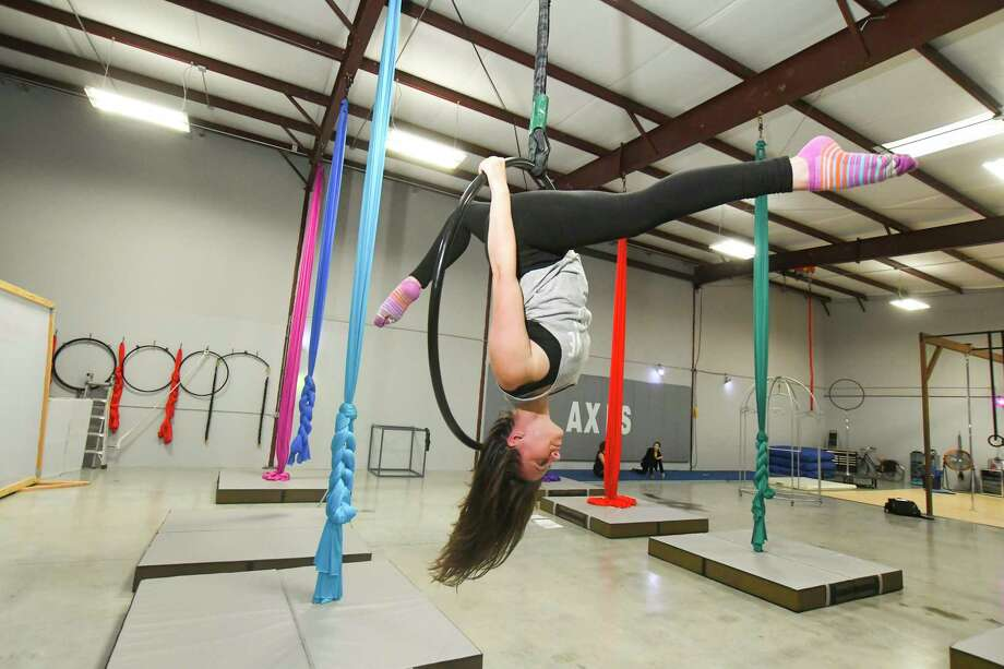 Rachel Tisdale is the owner of Axis Aerial Arts in the Cypress area. Twirling around on a pole or suspended in the air by colorful silks are just a few ways people are finding their fitness inspiration. Photo: Tony Gaines/ HCN, Photographer