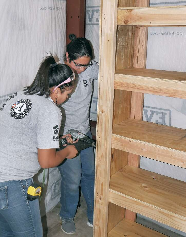 AmeriCorps Service members Kimberly Mata and Carlos Pardo work on a set of shelves that were built for the Salvation Army Thrift Store by Habitat for Humanity and AmericCorps Service members Jan. 15 as part of an MLK Day of Service event. Photo: Cuate Santos /Laredo Morning Times / Laredo Morning Times