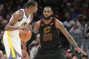 Cleveland Cavaliers forward LeBron James defends Golden State Warriors forward Kevin Durant in the third quarter Monday, Jan. 15, 2018 in Cleveland, Ohio. The Cavaliers lost to the Warriors 118-108.  (Leah Klafczynski/Akron Beacon Journal/TNS)