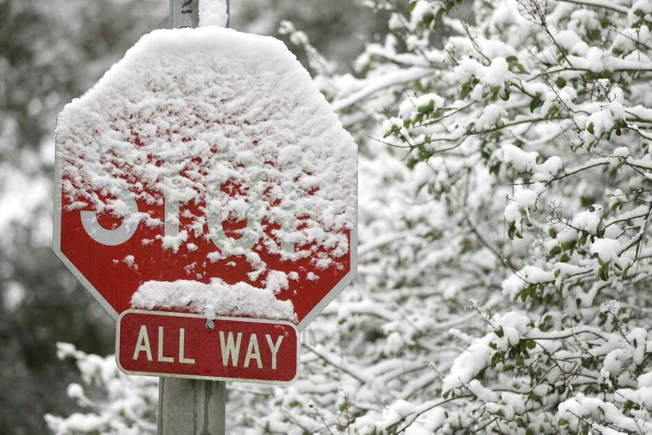 A snow covered stop sign is shown along Champion Dr. near Cypresswood Dr. Friday, Dec. 8, 2017, in Spring( Melissa Phillip / Houston Chronicle )