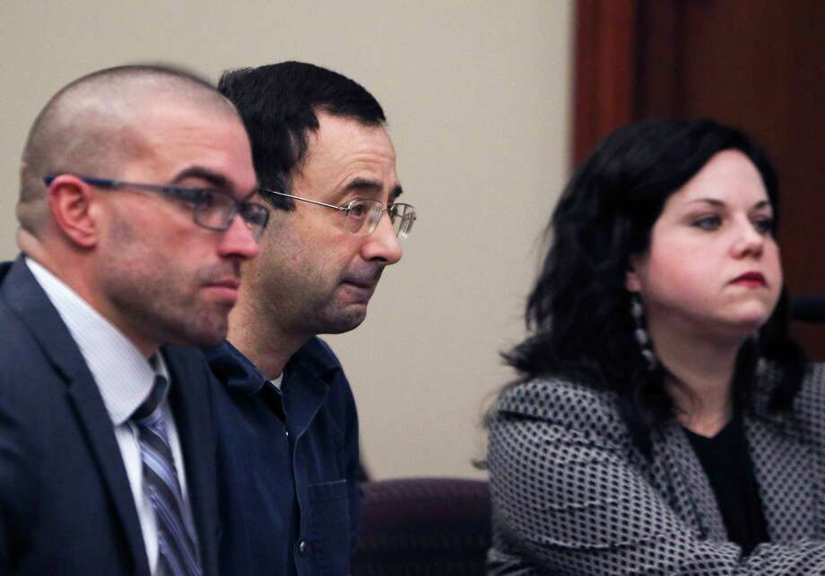 Larry Nassar arrives at court Tuesday, Jan. 16, 2018, for the first day of victim impact statements in Circuit Court Rosemarie Aquilina's courtroom in Lansing, Mich. Flanking Nassar are his attorneys Matt Newburg and Shannon Smith. Nassar pleaded guilty to molesting females with his hands at his Michigan State University office, his home and a Lansing-area gymnastics club. (Matthew Dae Smith/Lansing State Journal via AP) Photo: Matthew Dae Smith, AP / Lansing State Journal
