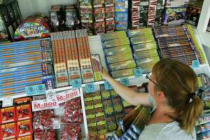 Karen Jurney, a fireworks stand manager, stocks Roman candles at the family stand on Highway 87 near China Grove in this 2015 photo. The China Grove City Council has voted to direct its city attorney to draft an ordinance under which fireworks sales would be allowed.
