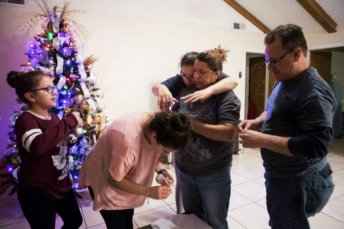 Kimberly Rodriguez, 11, Karen Rodriguez, 19, Rebecca Rodriguez, 16, pick ornaments to decorate their Christmas tree together, Friday, Dec. 1, 2017, in Houston.