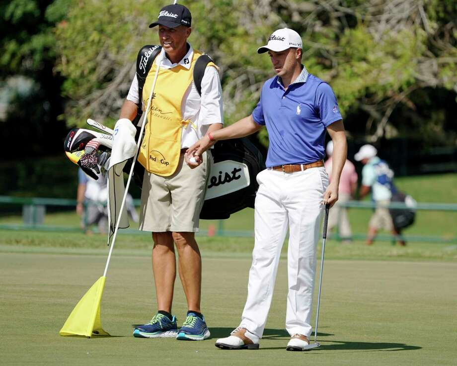 """Jim """"Bones"""" Mackay, left, takes the ball from Justin Thomas on the seventh green during the third round of the Sony Open golf tournament, Saturday Jan. 13, 2018, in Honolulu. Although he retired last year, MacKay is filling in for Thomas' injured caddie at the Sony Open. (AP Photo/Marco Garcia) Photo: Marco Garcia, FRE / 2018"""