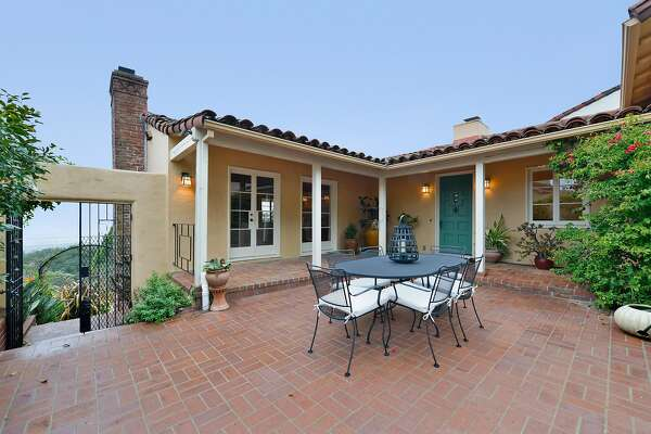The Mediterranean home features a brick chimney and tile roof.�
