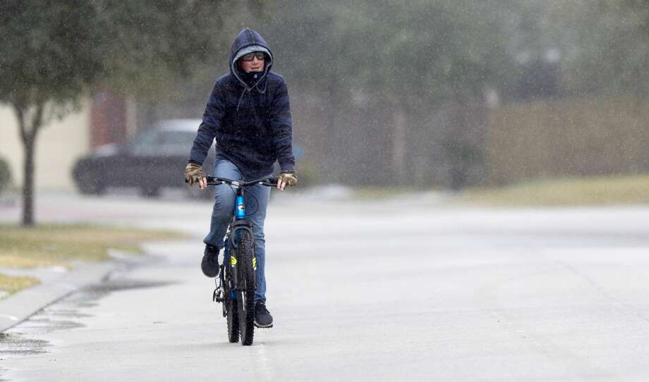 William Johnson, 14, rides his bike as sleet rains down after a winter storm brought freezing rain and ice throughout the greater Houston area, Tuesday, Jan. 16, 2018. The National Weather Service issued a Winter Storm Warning for southeast Texas until midnight Wednesday. Photo: Jason Fochtman/Houston Chronicle