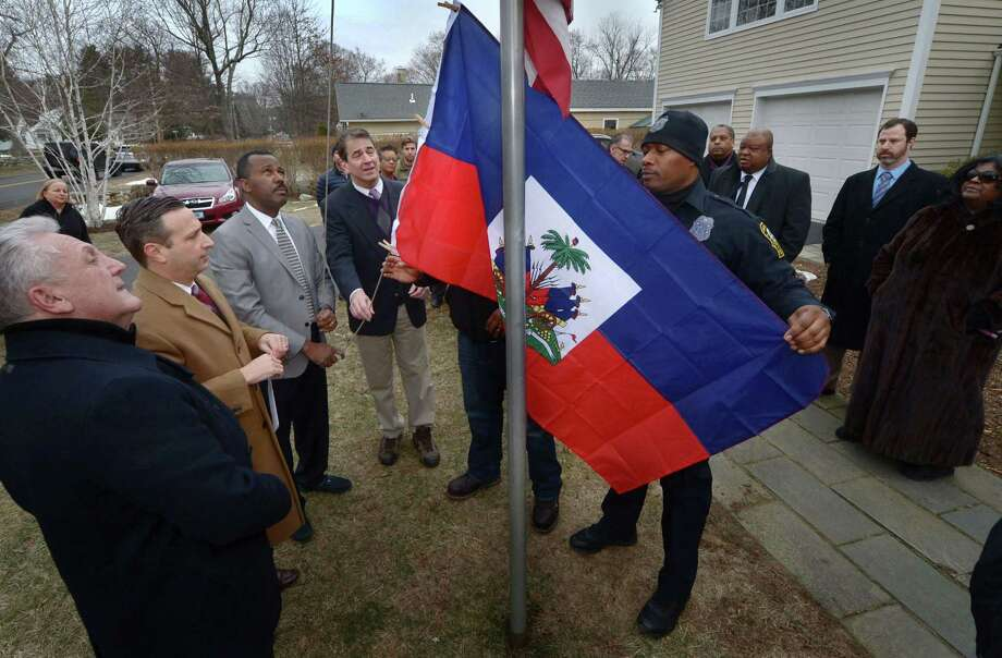 Norwalk Mayor Harry Rilling, Senate Majority Leader Bob Duff (D-Norwalk), members of the Haitian-American community including Guy Bocicaut and Police Officer Max Sixto, right, as well as State Rep. Chris Perone (D-Norwalk) raise the Haitian flag Tuesday, January 16, 2018, in an effort to show solidarity with the Haitian-American community at the home of Senator Duff in Norwalk, Conn. Photo: Erik Trautmann / Hearst Connecticut Media / Norwalk Hour