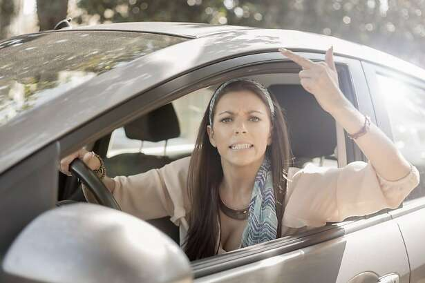 Young woman, driving, making hand gesture from open window