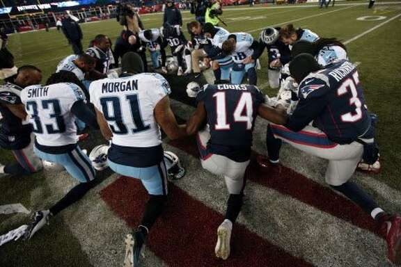 Tennessee Titans and New England Patriots players pray together at midfield after an NFL divisional playoff football game, Saturday, Jan. 13, 2018, in Foxborough, Mass. (AP Photo/Michael Dwyer)