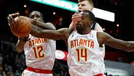 Atlanta Hawks' Dewayne Dedmon (14) and Taurean Prince (12) battle San Antonio Spurs forward Davis Bertans (42) for the ball in the first half of an NBA basketball game Monday, Jan. 15, 2018, in Atlanta.