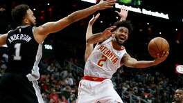 Atlanta Hawks guard Tyler Dorsey (2) goes up for as shot as San Antonio Spurs forward Kyle Anderson (1) defends in the second half of an NBA basketball game Monday, Jan. 15, 2018, in Atlanta. The Hawks won 102-99.