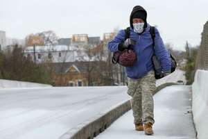 A man tries to stay warm as he walks on Hogan Street overpass above I-10 East Tuesday, Jan. 16, 2018, in Houston.