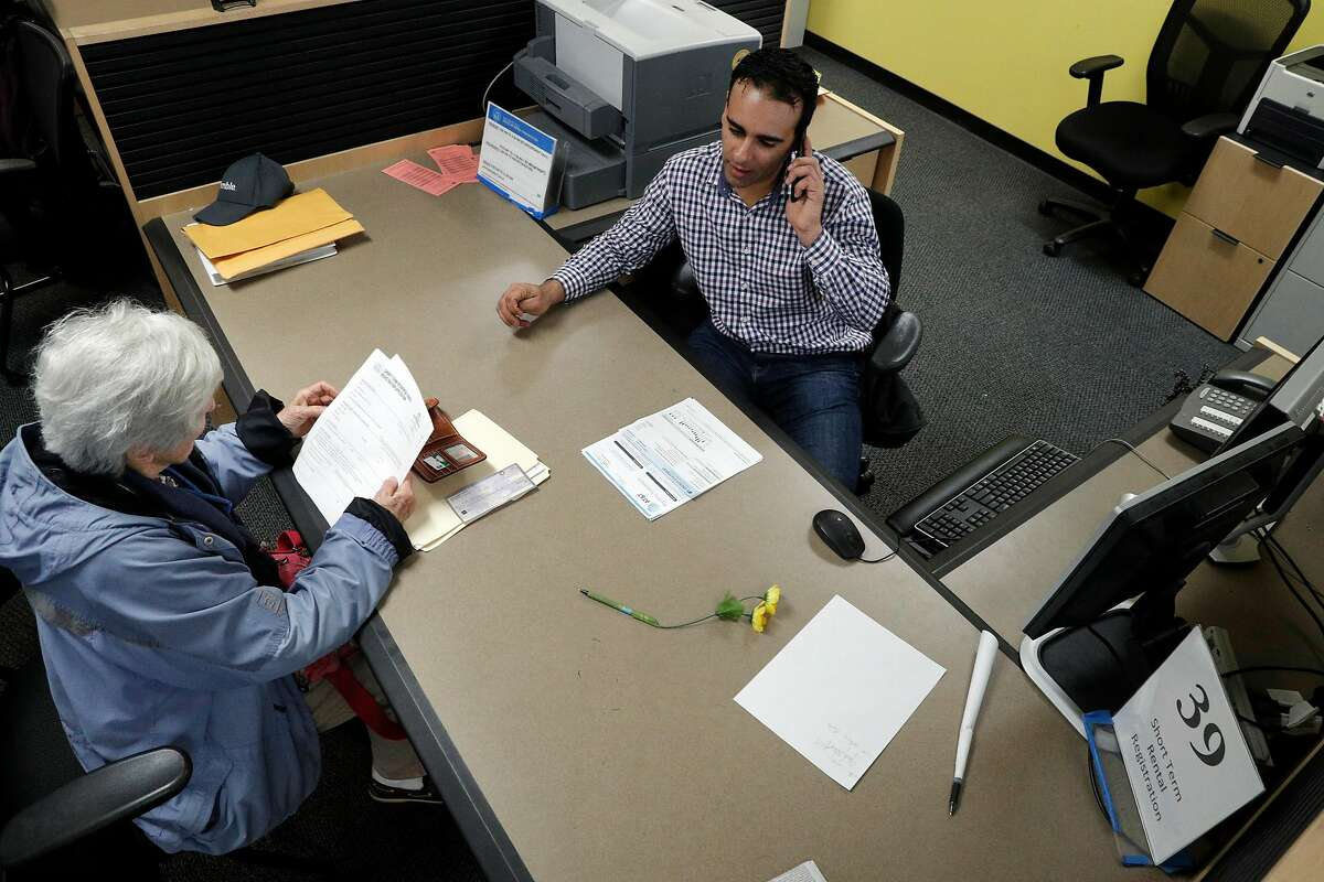 Senior Analyst Omar Masry helps Marcy Lipton with her paperwork for hosting guests at the Office of Short Term Rentals in San Francisco. After January 16, Airbnb and rival site HomeAway/VRBO are obligated to ditch any San Francisco hosts who've failed to register with the city, under terms of a legal agreement.