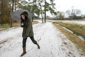 "Marie Hinke ""skates"" on ice wearing her cowboy boots, in Memorial Park, Tuesday, Jan. 16, 2018, in Houston. A winter storm moved into area bringing freezing rain and reports of snow. ""I'm not too familiar with frozen rain, because I'm from Houston,"" Hinke said."