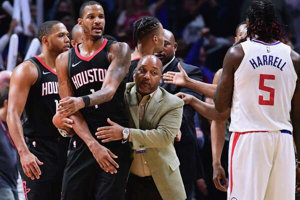 Not exactly seeing eye to eye with L.A.'s Montrezl Harrell, the Rockets' Trevor Ariza (1) is restrained by Bryant Savage of team security before his ejection Monday.
