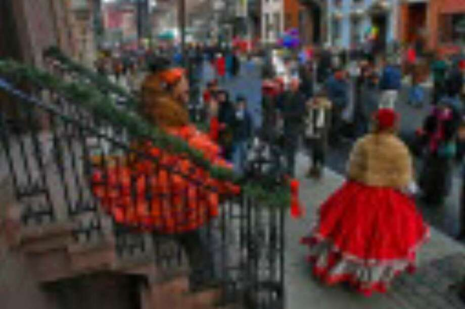 Lydia Zotto of Troy, center with orange hat, wears a Victorian dress made by her mother Deborah, far right in dark coat with camera to her eye. Claire Yingling of Ohio, is at lower right, and K'Drea Fox of Albany, is just behind Lydia, during the 27th annual Victorian Stroll in Troy Sunday. They were descending a staircase onto Second Street. Lydia, 21, has been taking part in the event since she was 10, wearing her mom's dresses the past 6 years. She and Claire, who both attend the Eastman School of Music at the University of Rochester, were to play harp later in the afternoon at the Rensselaer County Historical Society, down the street. (Philip Kamrass / Times Union)